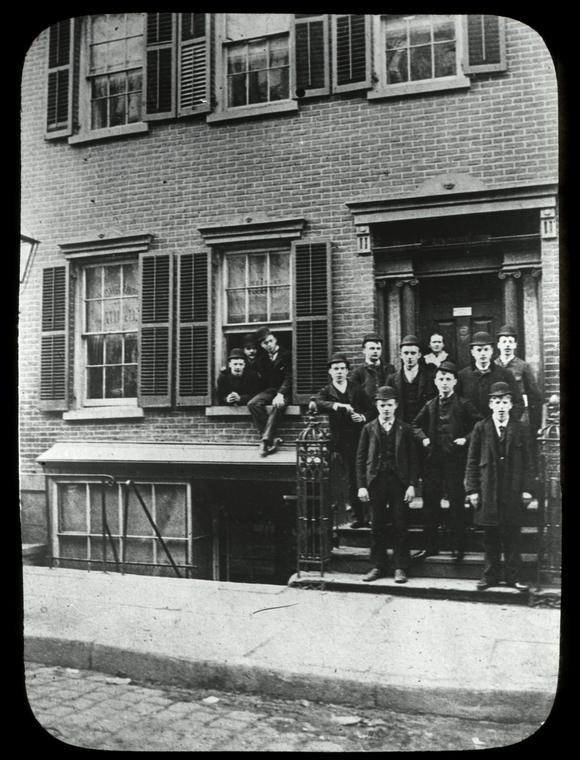 """Rivington Street, young men in front of """"147 Forsyth St. Neighborhood Guild Library in hall bedroom over front door,"""" parent of Rivington St. Branch, Digital ID 100879, New York Public Library"""