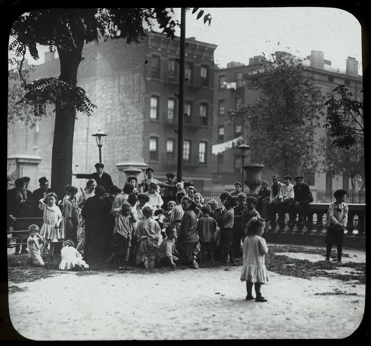 men listen along with children to story in the park, neighborhood buildings visible beyond, ca. 1910s.Courtesy of the New York Public Library