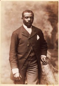 [Studio portrait of a man dressed in jacket, vest, tie and striped pants.]