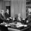 Arthur Byron (seated) as Nordson, with members of the Executive Committee: J.P. Wilson (as Mr. Osso), George Fogle (as Mr. Ciring) and Harold Thomas (as Dr. Wolff).
