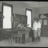 Williamsbridge, Two boys standing at desk where librarian is seated and writing, Sub-branch