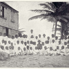 """Nevis; """"We seat them to be photographed with the school mistress in the back."""""""
