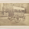 Howard ambulance, rear and side view, tailgate up, on city street.]