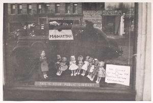 [Exterior, window display: Dolls Dressed by Girl Scout Troop 194.]