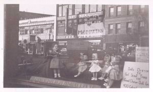 [Exterior, window display: Dolls Dressed by Girl Scout Troop 194.]