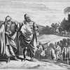 [Man and masked woman standing on hill observing people below.]