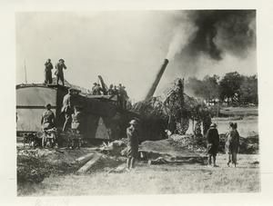"The American Advance in the Argonne region. American 14"" gun caught at the moment the huge shell left on its 20 mile journey to a German troop concentration point in the Argonne. The men are shown protecting their ears from the terrific noise."