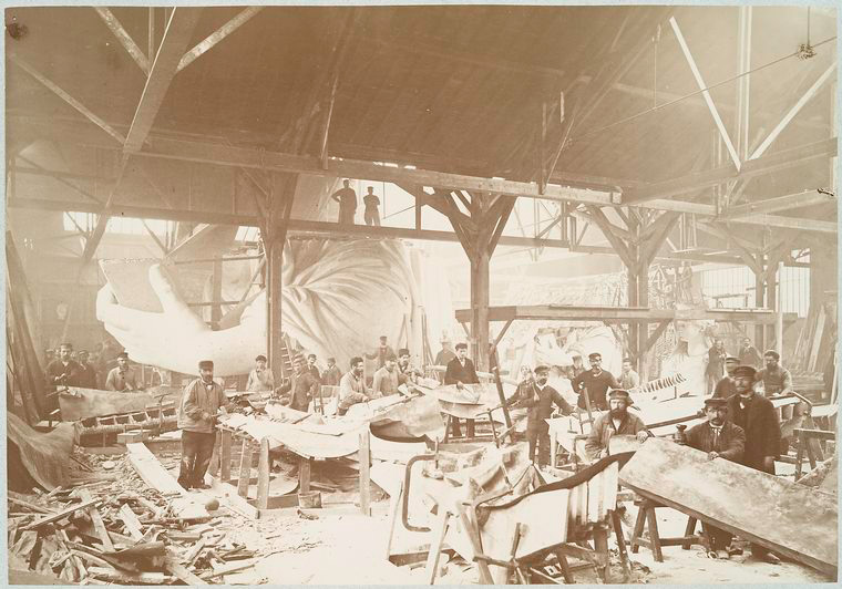 [Men in a workshop hammering sheets of copper for the construction of the Statue of Liberty.]