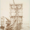 Assemblage of the Statue of Liberty in Paris, showing the bottom half of the statue erect under scaffolding, the head and torch at its feet.]