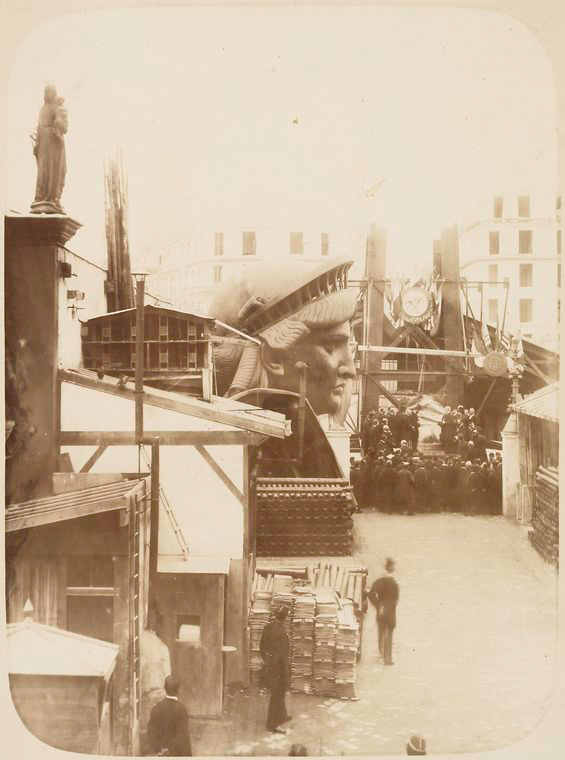 [View of the external area of the workshop in Paris, showing construction materials, the head of the Statue of Liberty, and a group of men gathered in front of the left foot of the statue.]