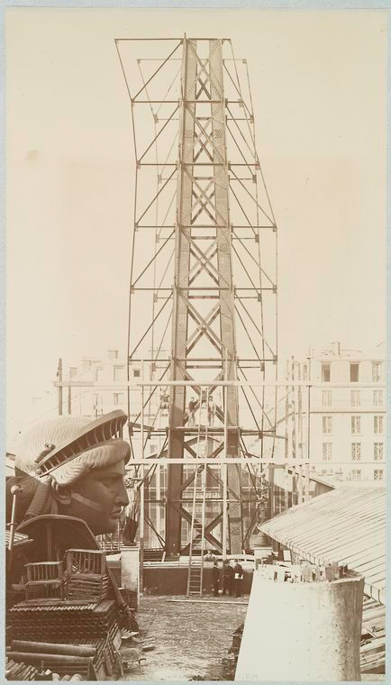 [Scaffolding for the assemblage of the Statue of Liberty, of which the head is shown at left, in Paris.]