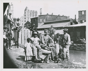 [Group of freedmen, including children, gathered by a canal in Richmond, Virginia, in 1865.]