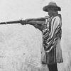 A Gora man firing gun from armpit