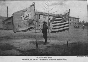 Guarding the flag; The flag of the old 15th (decorated by the French) and Old Glory.