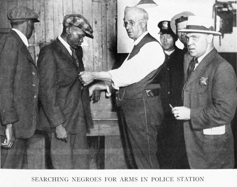Searching Negroes for arms in police station.