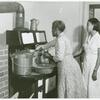 Ada Turner and Evelyn M. Driver Home Management and Home Economics Supervisor, canning English peas with pressure cooker in Mrs. Missouri Thomas' kitchen, Flint River Farms, Georgia, May 1939.