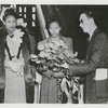 Beulah Whittington, an African American shipyard worker, receiving a bouquet of American Beauty roses from Frank Stearns of Richmond Shipyard No. 2 as Katie Lewis, the African American matron of honor, looks on during the ship launching of the SS S. Hall Young at Richmond Shipyard No. 2