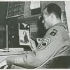 African American Master Sergeant William P. Thompkins sitting at a desk and looking at a photograph of his fiancée Delores Taylor, Fort Dix, New Jersey