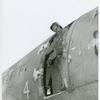 African American Sergeant James C. Snowden of the 555th Parachute Infantry Battalion standing in the doorframe of a C-47 transport plane, preparing to jump