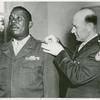 Colonel R. L. Salzmann pins a first Lieutenant's bar on the shoulder of African American Lieutenant Jesse J. Holbert