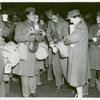 Red Cross worker pouring coffee into the cup of an African American member of the Women's Army Corps as other African American WACs stand with their coffee and doughnuts and look on, Staten Island Terminal, New York Port