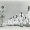 African American recruits in sailor uniforms walking in rows and passing in review before Lieutenant Commander Daniel W. Armstrong