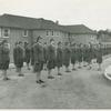 Army nurses standing at attention in front of their barracks and being inspected by staff officers, Army nurse training center, England