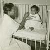 African American nurses' aide feeding an African American infant