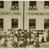 """[Delegates in front of building, """"Kunzjozsef es Tarsa Fehernemugyara."""".]"""