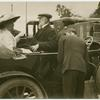 [Unidentified man and woman sitting opposite one another in a motorcar.]