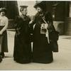 Two women in conversation on the street.]