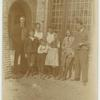 [Group portrait in front of house.]