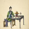 Woman seated at table, playing a xiao.]