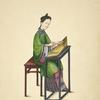 Woman seated at table, playing a zheng.]