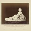 [Statue of nude woman holding cup and laying on animal skin.]