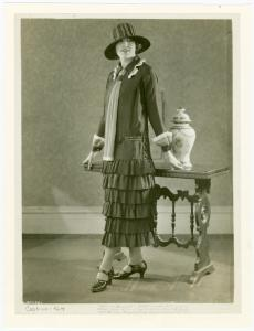 [Woman in navy dress and hat posing next to a table.]