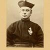 Priest in biretta and cassock]