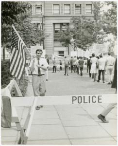 [Leo Skir with American flag in picket line] / Kay Tobin Lahusen