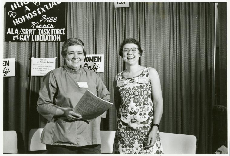 black and white image of two eomen, smiling, underneath a sign that says hug a homosexual.