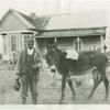 Man with mule in front of farmhouse]