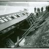 Overturned train car with broken windows]