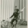 Amusements - American Jubilee - Scenes - Bicycle Number - Ray Middleton and Selma Hoffman on bicycle