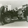 Automobiles - Ye Goode Olde Days - Man pumping tire while woman waits