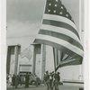 Flags - Men pulling down American flag outside of Australian Pavilion