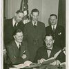 German Consul General, Johannes Borchers, signing contract with Grover Whalen while officials look on
