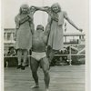 Strongman John Grimek holds up two girls