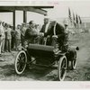 General Motors - William S. Knudson in car shaking hands with man