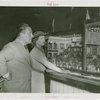 Grover Whalen and Anna Neagle inspecting dollhouse
