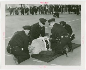 New York City - Police Dept. - Policeman demonstrating giving first aid to victim