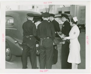 New York City - Police Dept. - Policeman demonstrating moving victim into ambulance